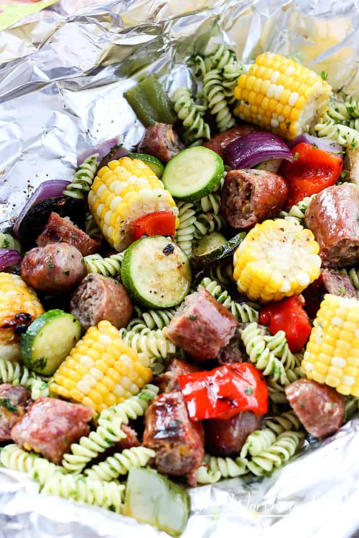 We're celebrating #bratsgiving with a fun twist on the classic crab + shrimp boil foil packets recipe by using pasta with herbs, bratwurst, and fresh veggies.