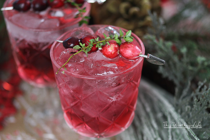 Celebrate the holiday with this fun holiday mocktail drink idea. It's filled with cranberries, sparkling juice and mint mixed all together to make a Cranberry Spritzer.