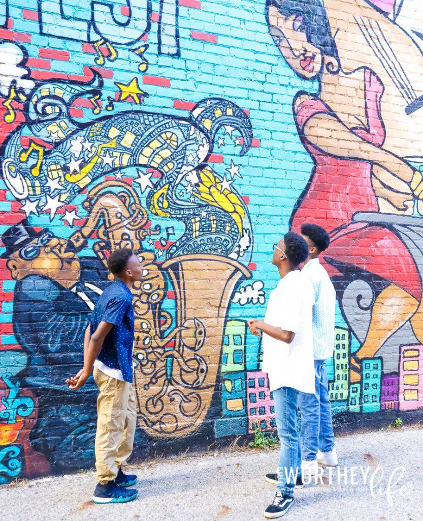 three african american teenagers looking at mural