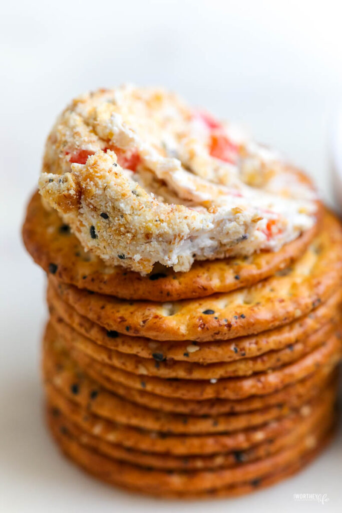 a stack of crackers with the top cracker topped with a smeared cheese ball