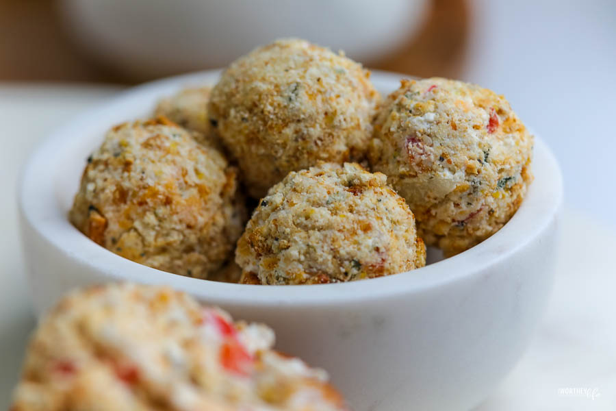 a white stone bowl filled with mini cheese ball rolled in cracker crumbles