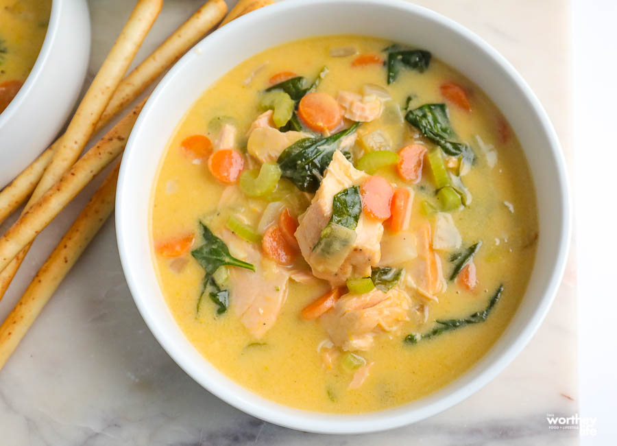 white serving bowl filled with delicious salmon and spinach soup