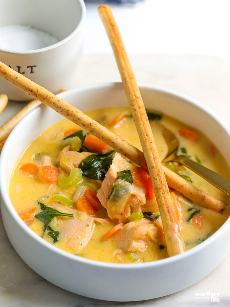 a white porcelain bowl with warm salmon soup and two crossed breadsticks