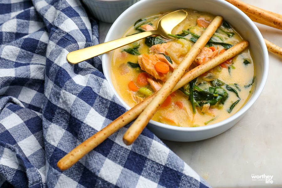 a bowl filled with hot salmon soup with spinach