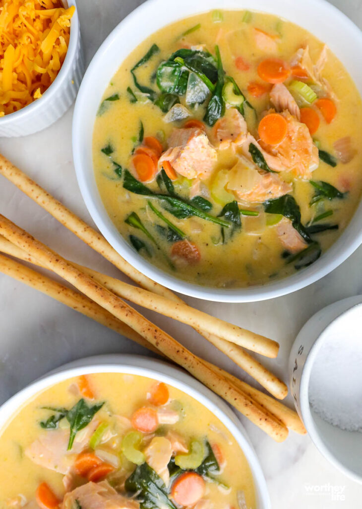 bowls with salmon soup and long breadsticks