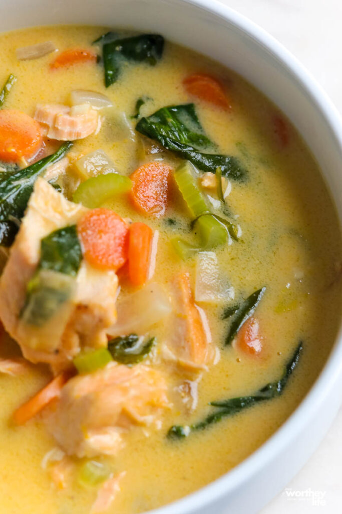 creamy spinach salmon soup in a white bowl close up