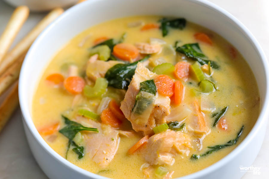 a white bowl filled with salmon and spinach soup