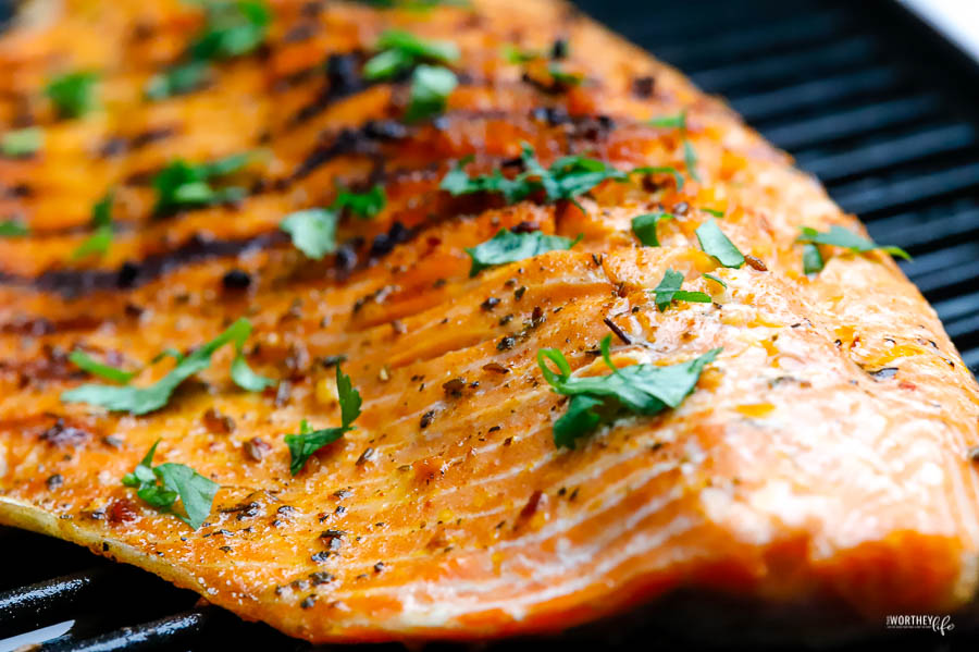 a large filet of cooked salmon with grill marks and topped with chopped cilantro