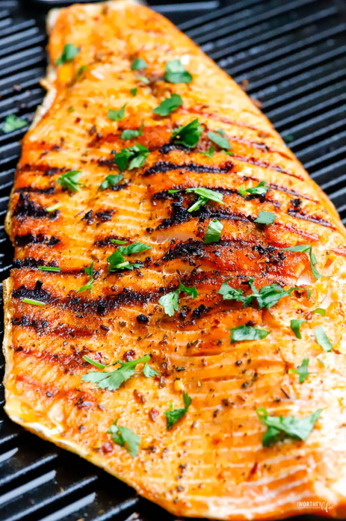 large slab of salmon laying cooked on grill