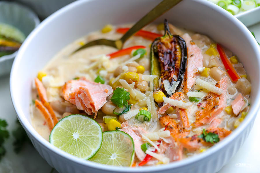 white bowl with white bean chili and salmon. topped with green onion and two wedges of lime