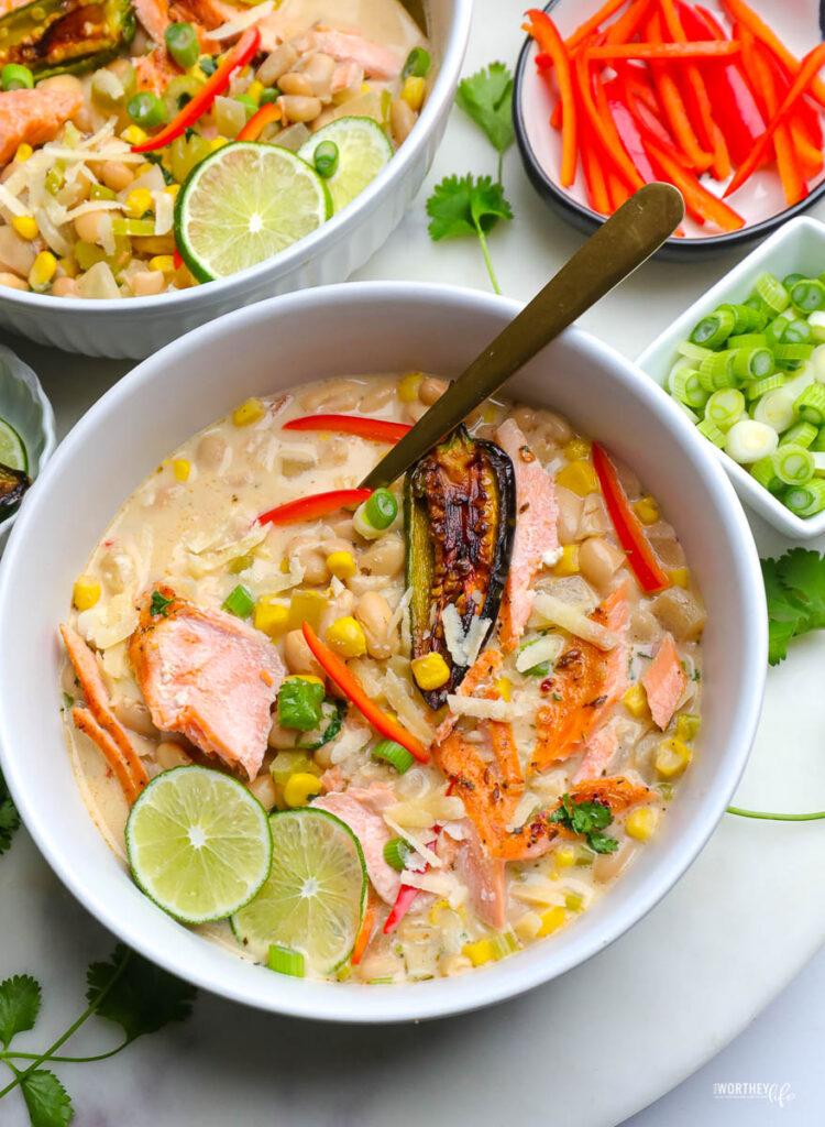 white chili salmon in a white bowl with fresh veggies