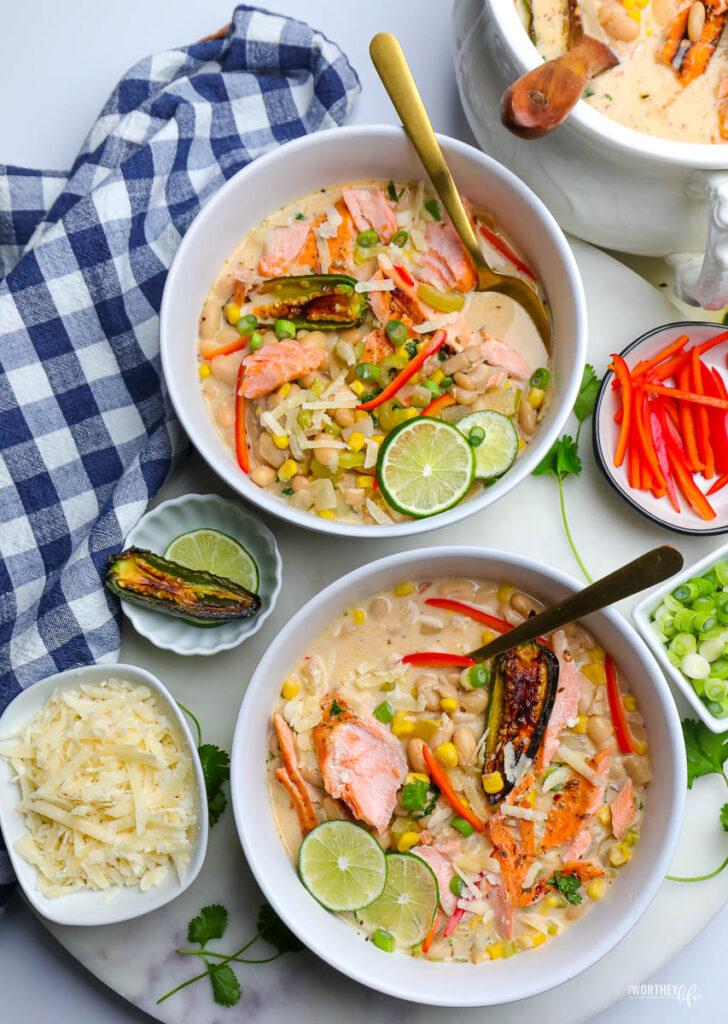 two white bowls of white chili salmon on white background with blue napkin