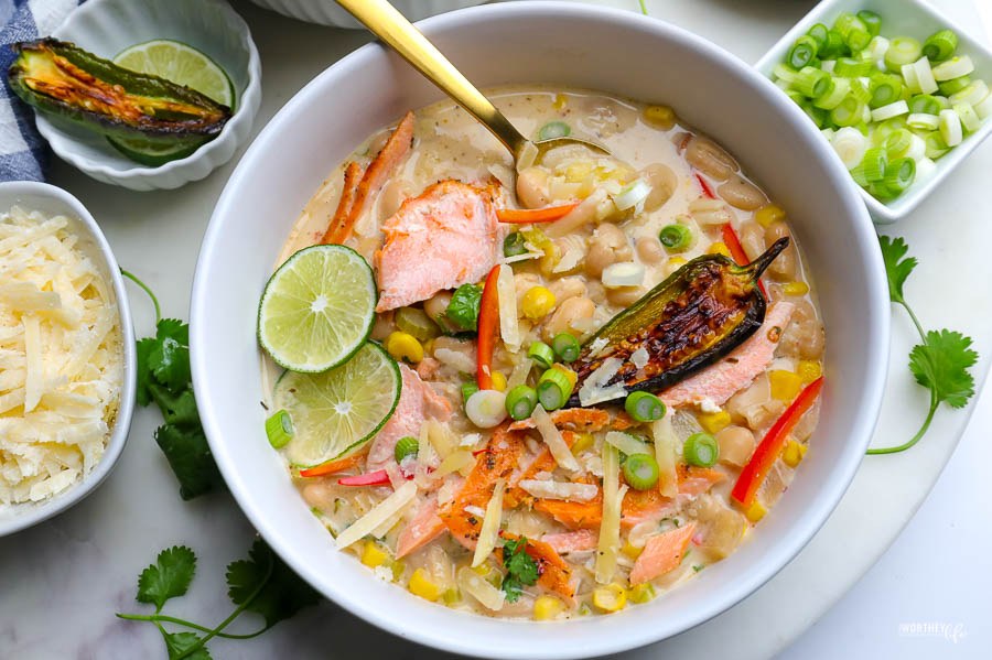 white bowl with white bean chili and salmon. topped with green onion and wedges of lime